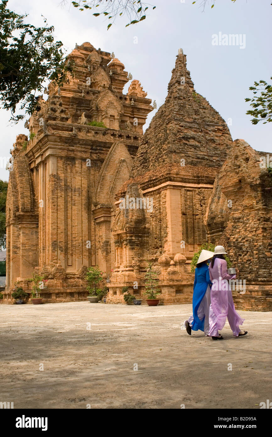 Women walk in front of the Po Nagar Towers at Nha Trang in Vietnam. - Stock Image