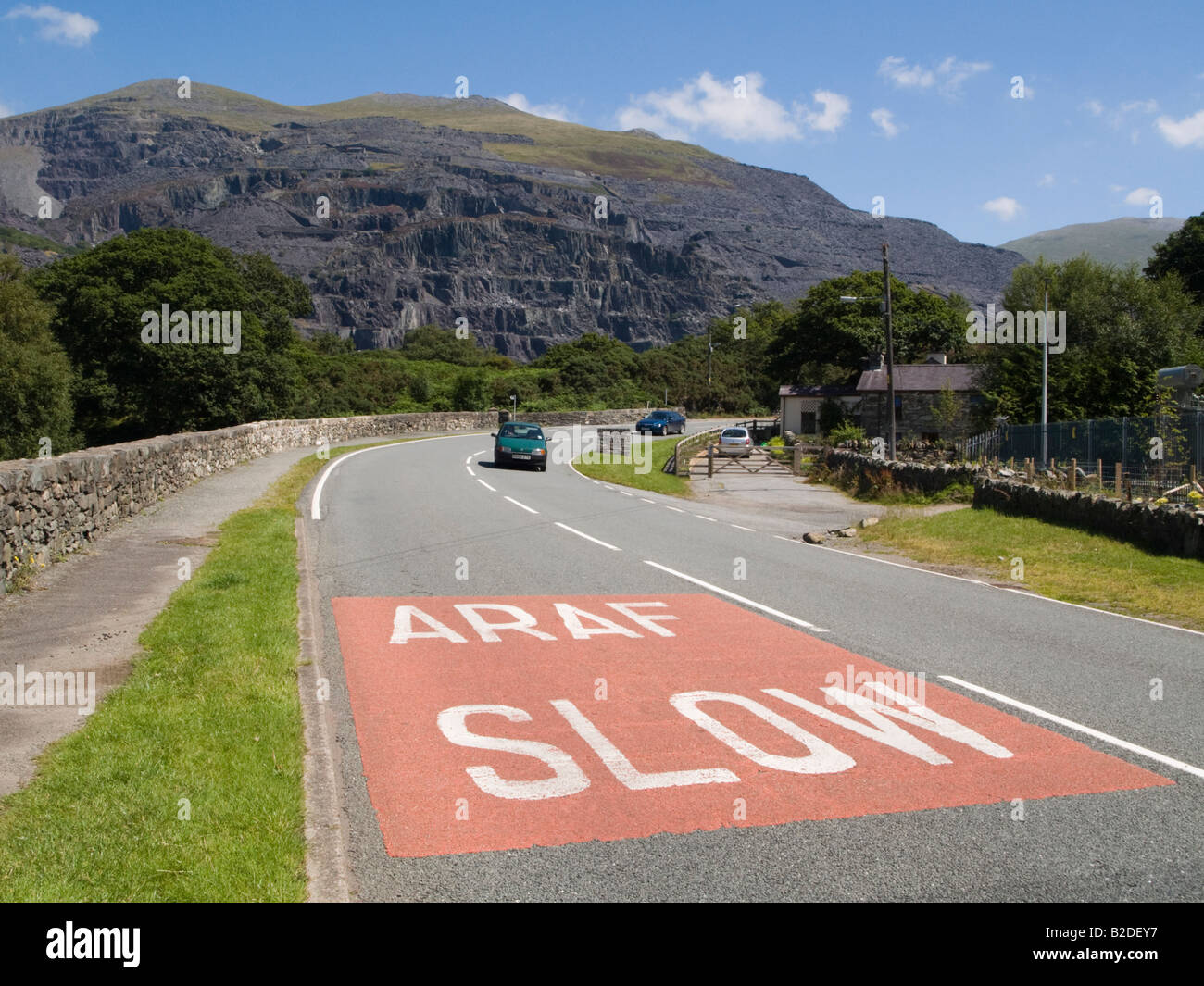Bilingual Araf Slow sign in Welsh and English painted on a road surface before a bend near Llanberis Gwynedd North - Stock Image