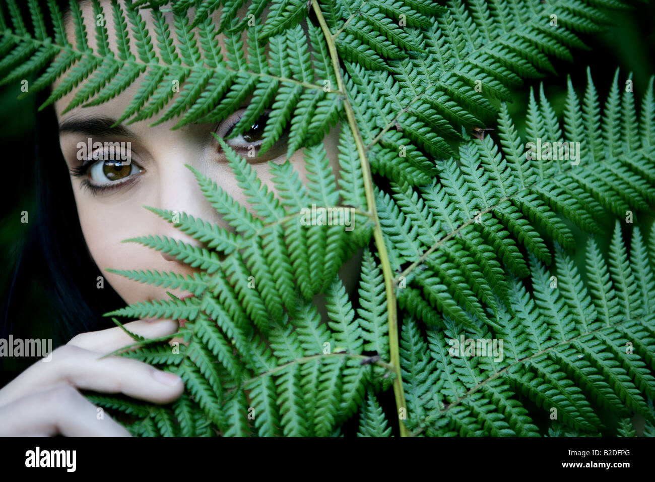 Young woman behind leaves. - Stock Image