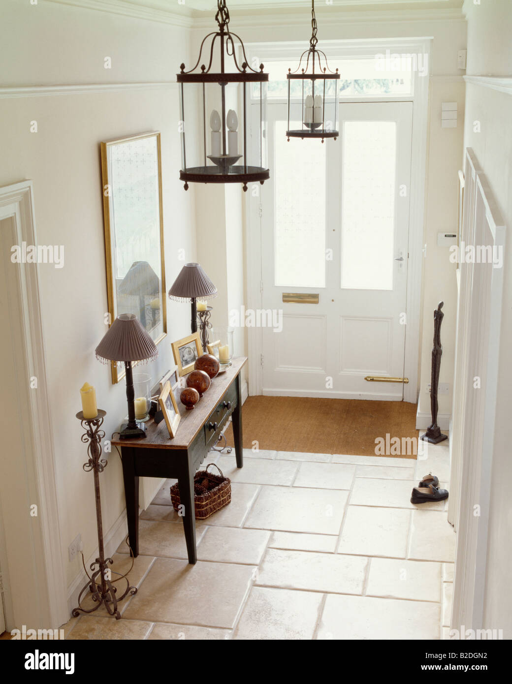 Limestone floor tiles in white hall with lantern lighting and lamps ...