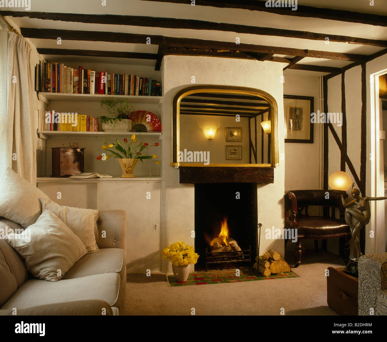 small cottage living room large mirror above small fireplace in beamed cottage 16618