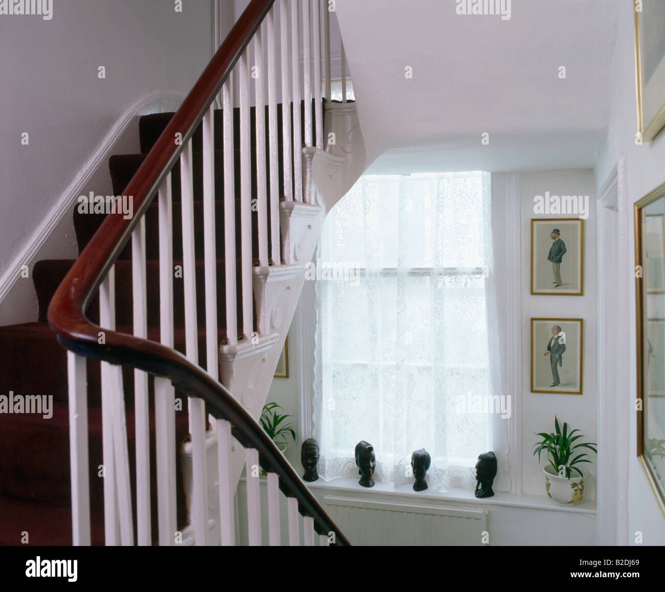 Mahogany Rail And White Banisters On White Staircase Stock