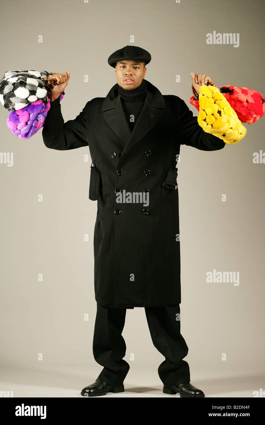 Young African American man holding stylish purses. - Stock Image