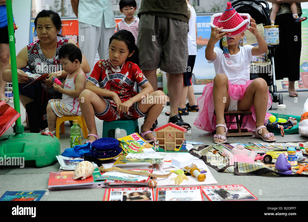Teenages sell uesd goods at flea market on Sunday in a community in Beijing, China. 26-Jul-2008 - Stock Image