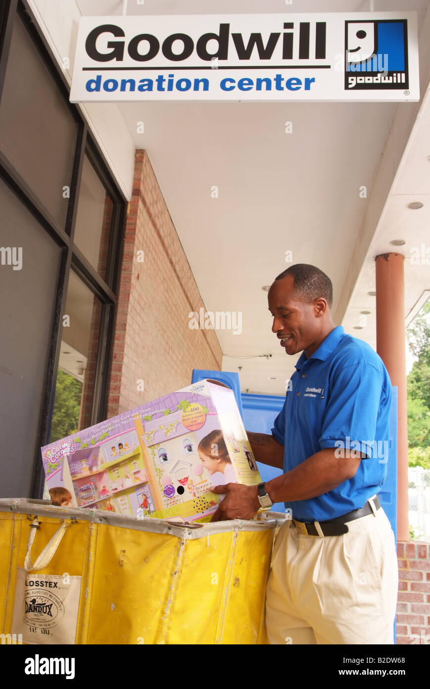 Employee of Goodwill Industries puts a donated toy into a receiving bin at their collection center, Maryland EDITORIAL - Stock Image