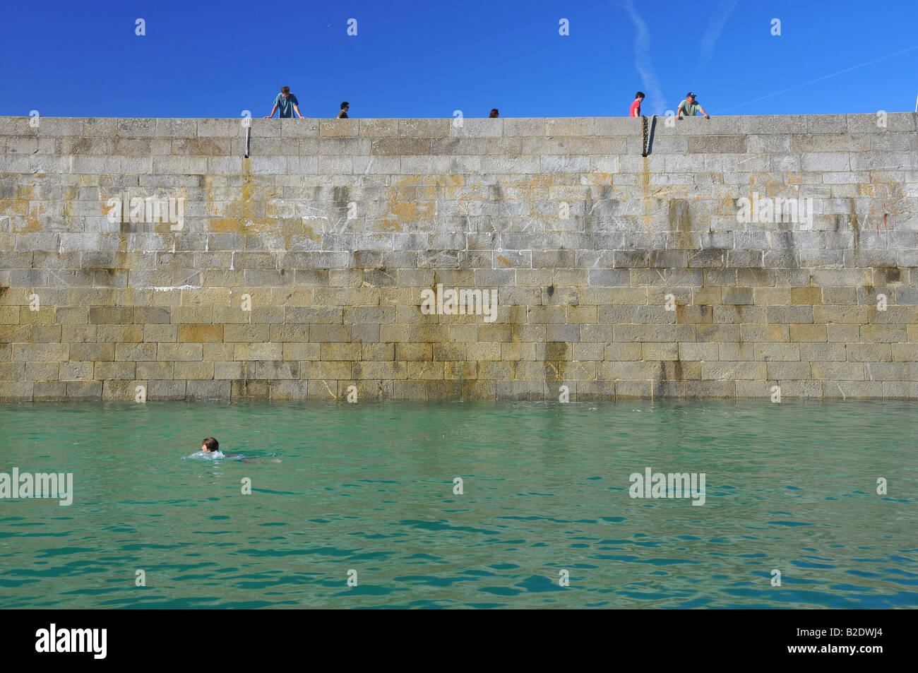 people on a high deck looking at a swimmer downwards by a sunny day - Stock Image