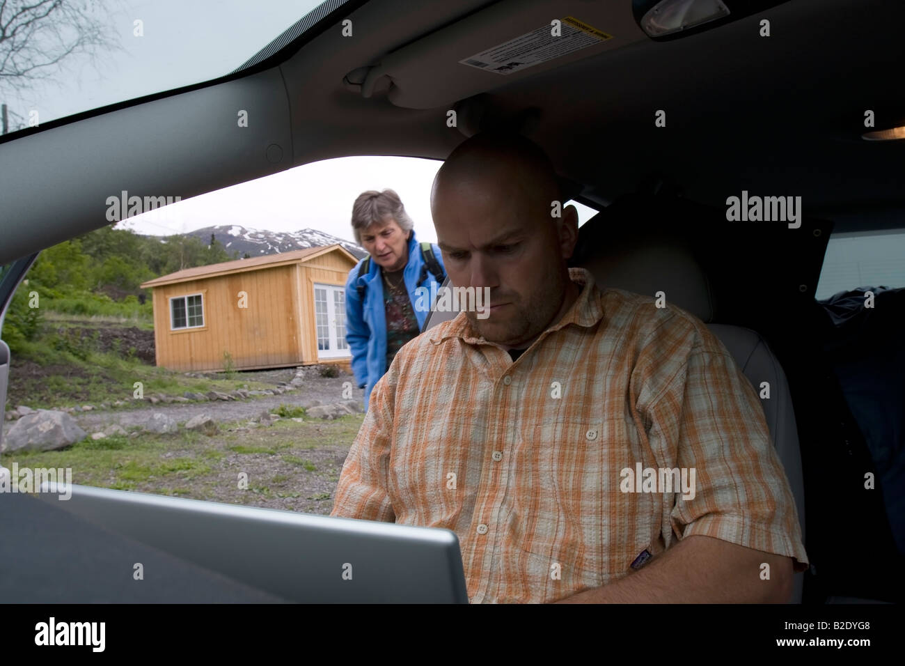 Photographer using mobile office in a car to upload photos to agencies, Palmer, Alaska, United States of America - Stock Image