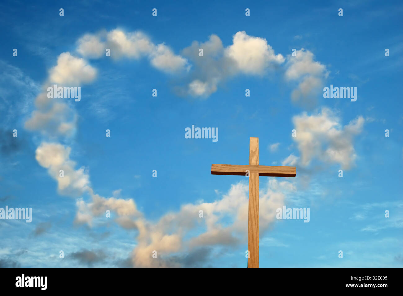 wooden cross and heart shaped clouds in the background stock photo