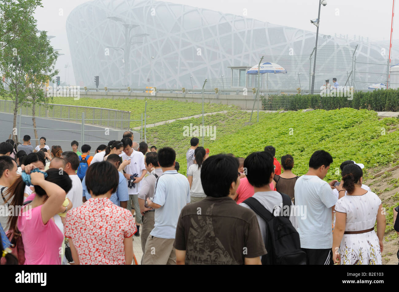 Chinese tourists look at National Stadium in a haze in Beijing, China. 27-Jul-2008 - Stock Image