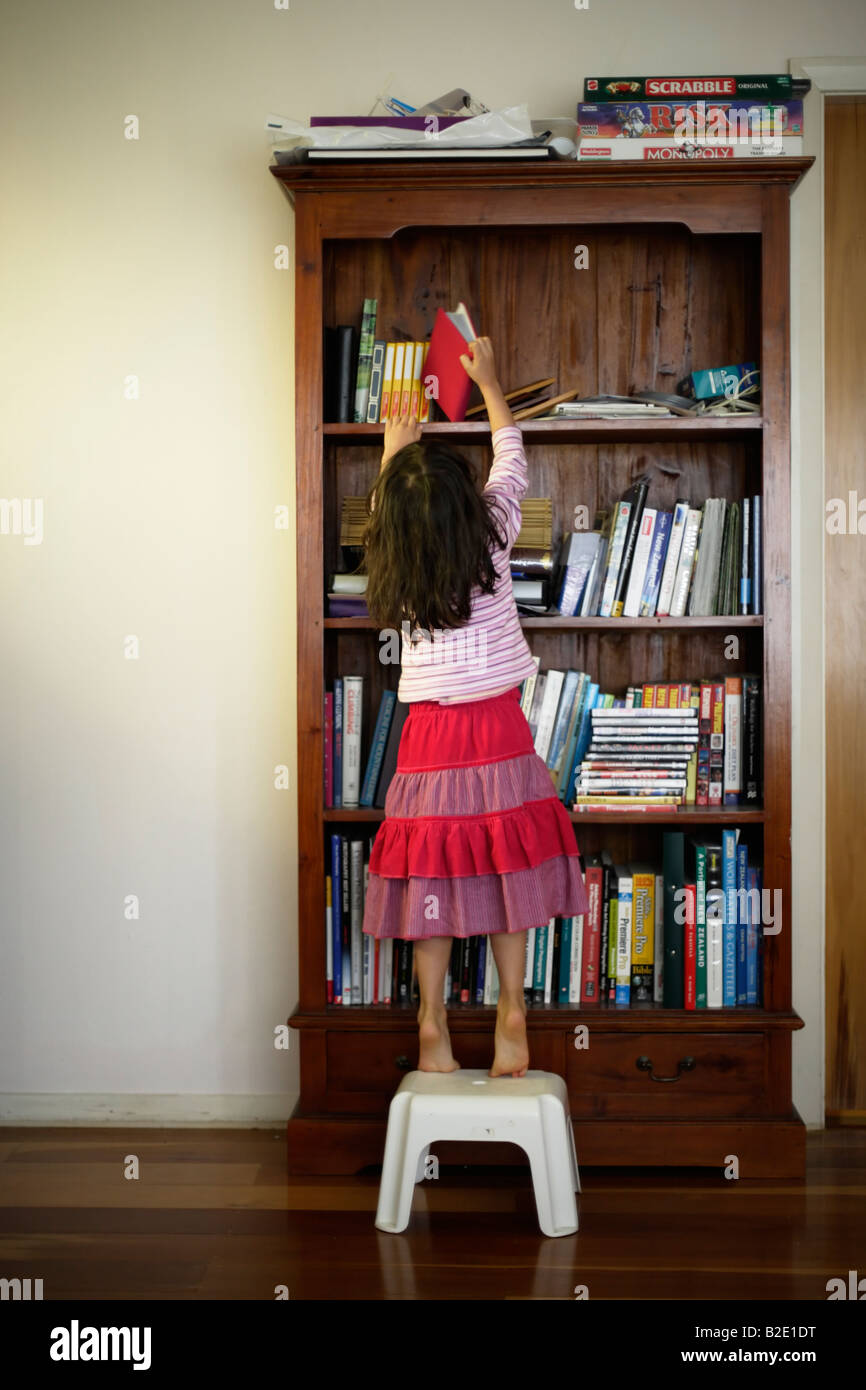 Five year old girl uses steps to reach book in bookcase - Stock Image