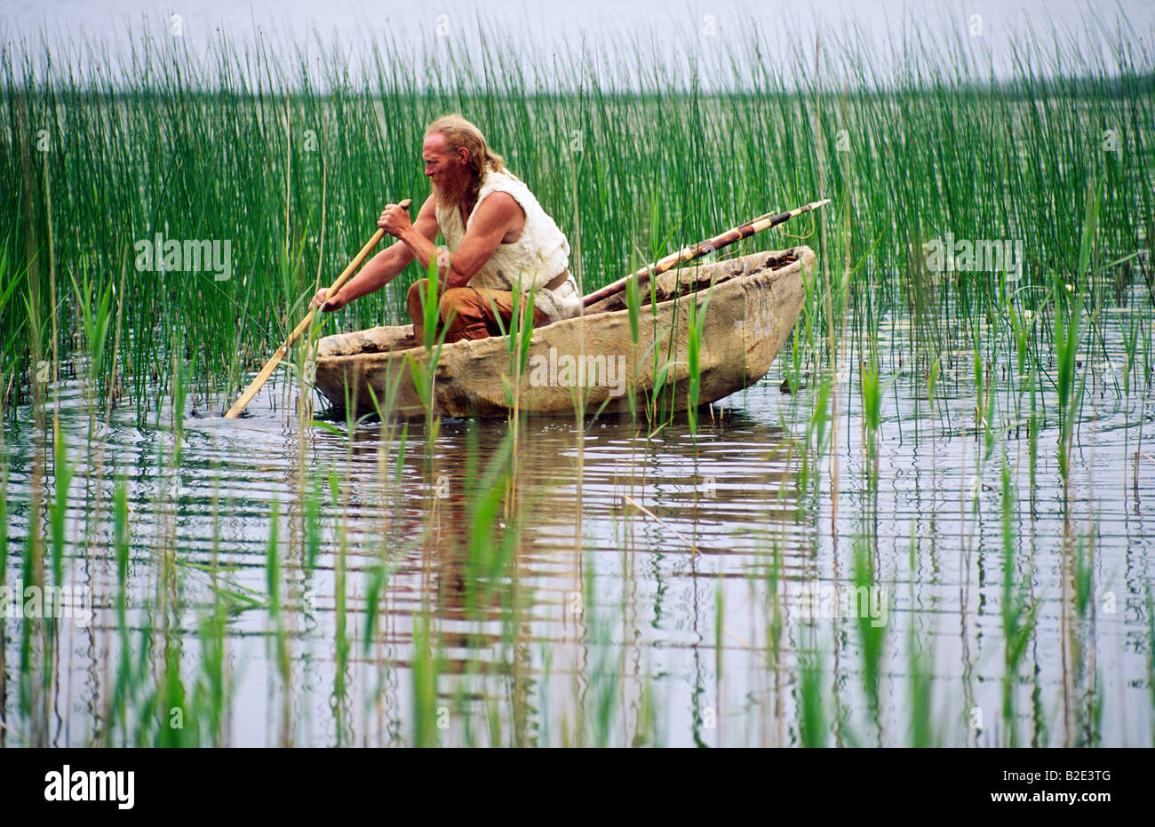 Neolithic re-enactment. Stone Age man with fish spear paddling animal hide coracle boat on reed shore lake. Kilmartin, - Stock Image