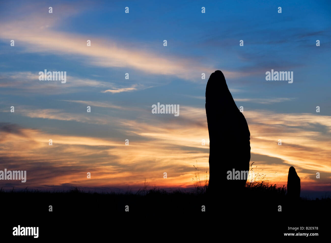 Avebury standing stones against a sunset. Silhouette - Stock Image