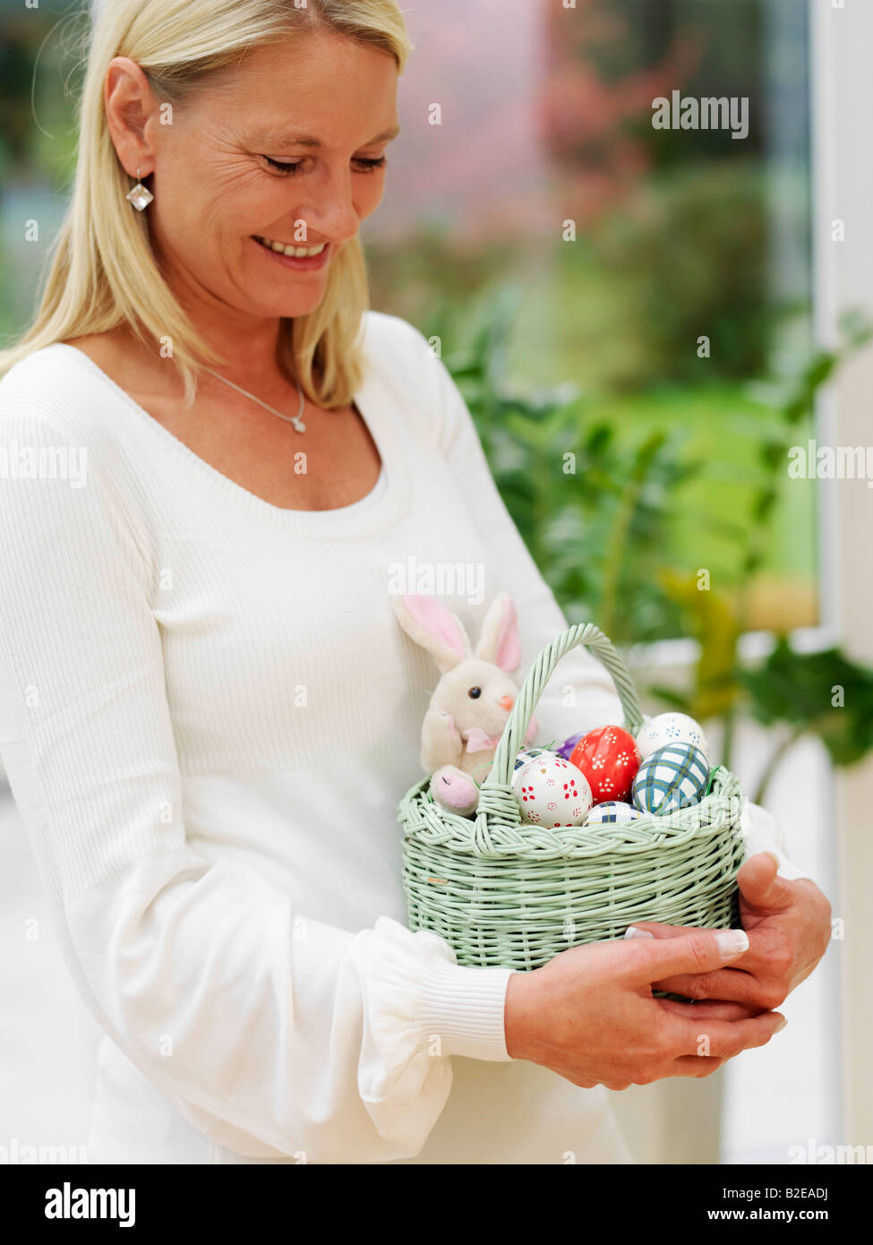 Close-up of woman carrying basket of Easter eggs - Stock Image
