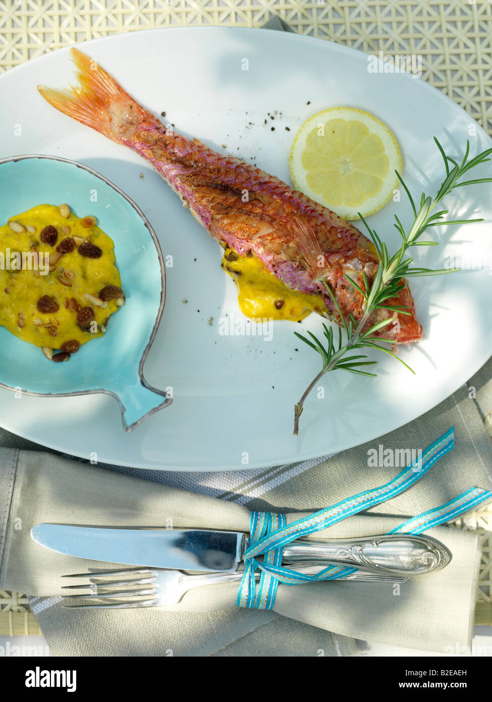 Fish and slice of lemon with savory sauce on plate - Stock Image