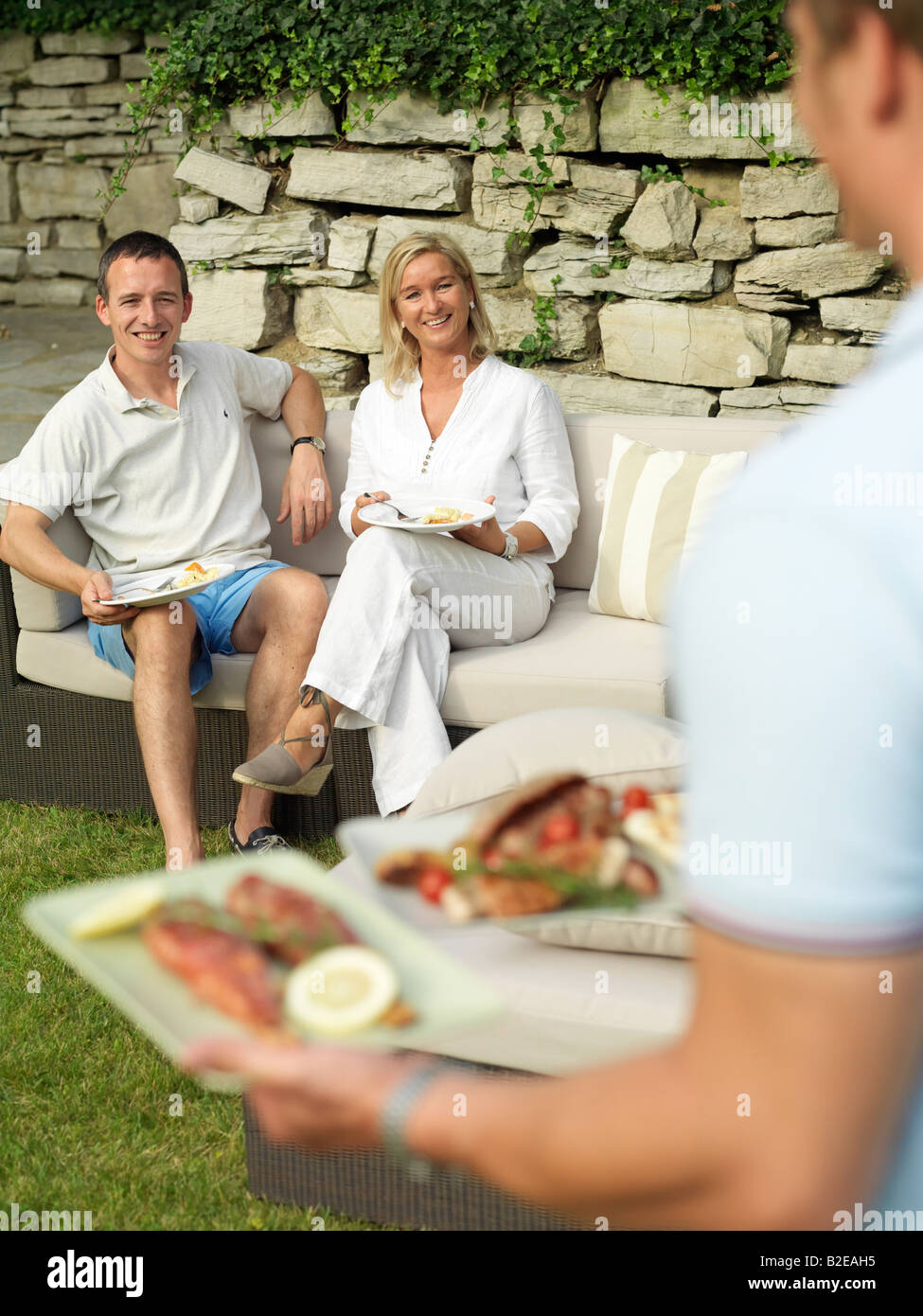 Couple looking at man carrying prepared fish of plates - Stock Image