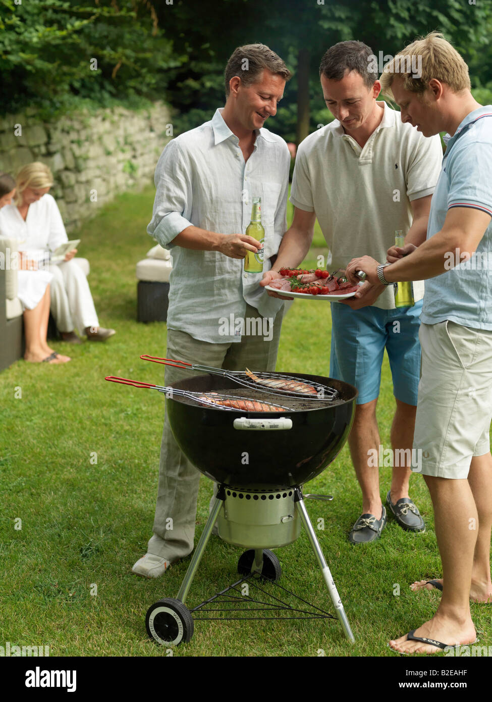 Three men preparing fish on barbeque grill in garden - Stock Image