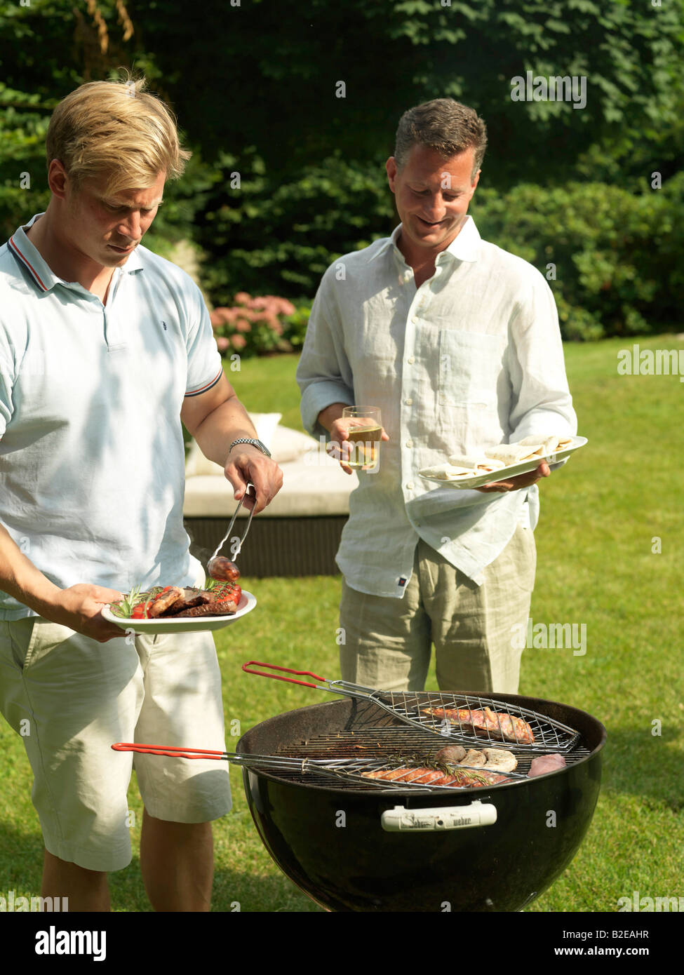 Two men preparing fish on barbeque grill in garden - Stock Image