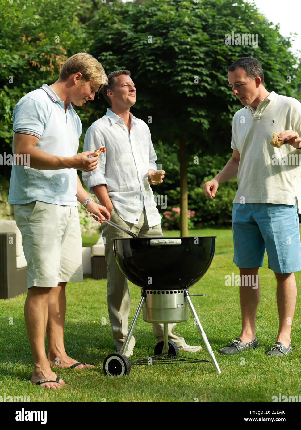 Group of men having barbecue - Stock Image