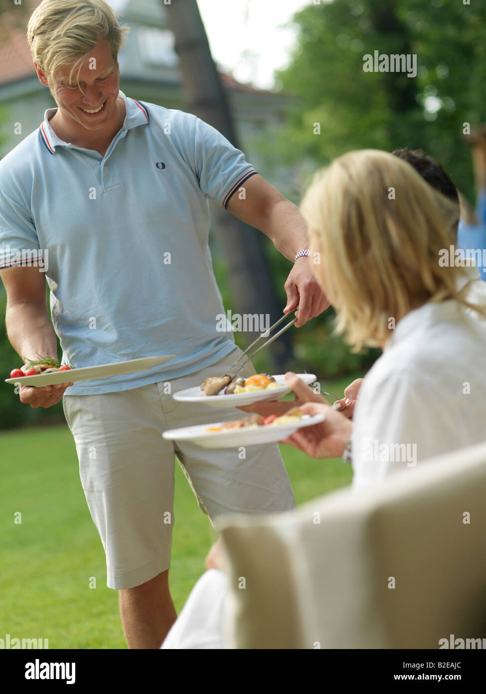 Man serving food to his friends at a garden party - Stock Image