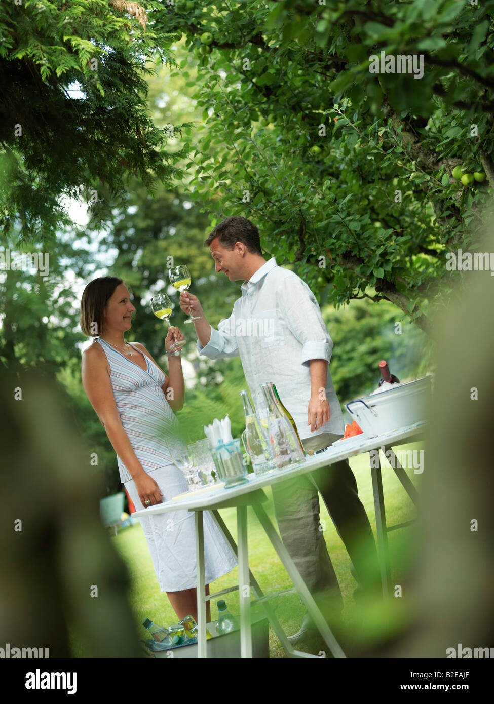Couple toasting with wineglasses in garden - Stock Image