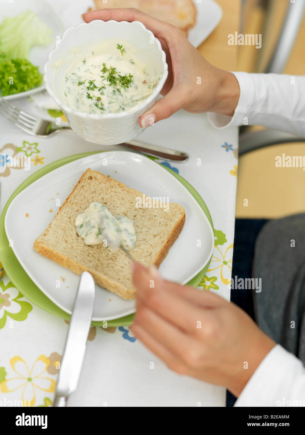 Person's hands spreading cream cheese on slice of bread - Stock Image