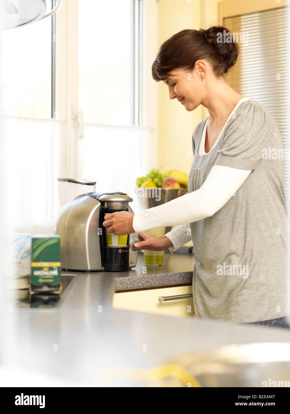 Side profile of young woman using coffee maker in kitchen - Stock Image