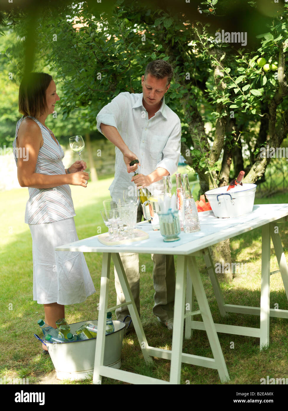 Woman looking at man opening bottle in garden - Stock Image