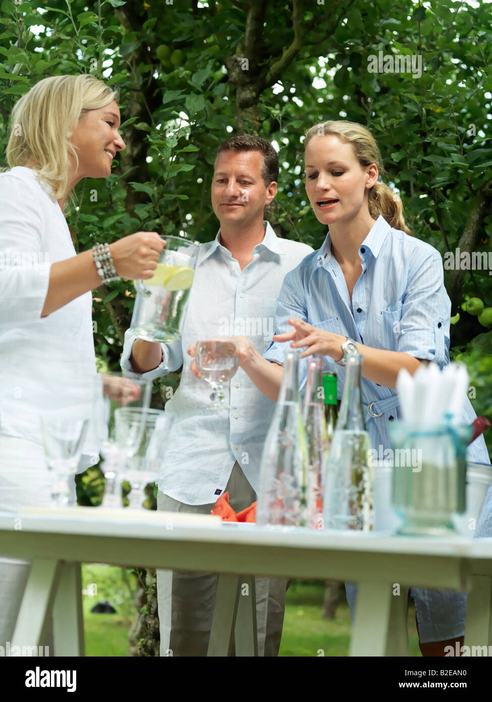 Low angle view of woman serving water to her friend - Stock Image