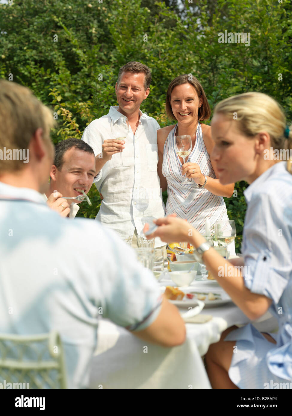 Three couples celebrating at a garden party - Stock Image