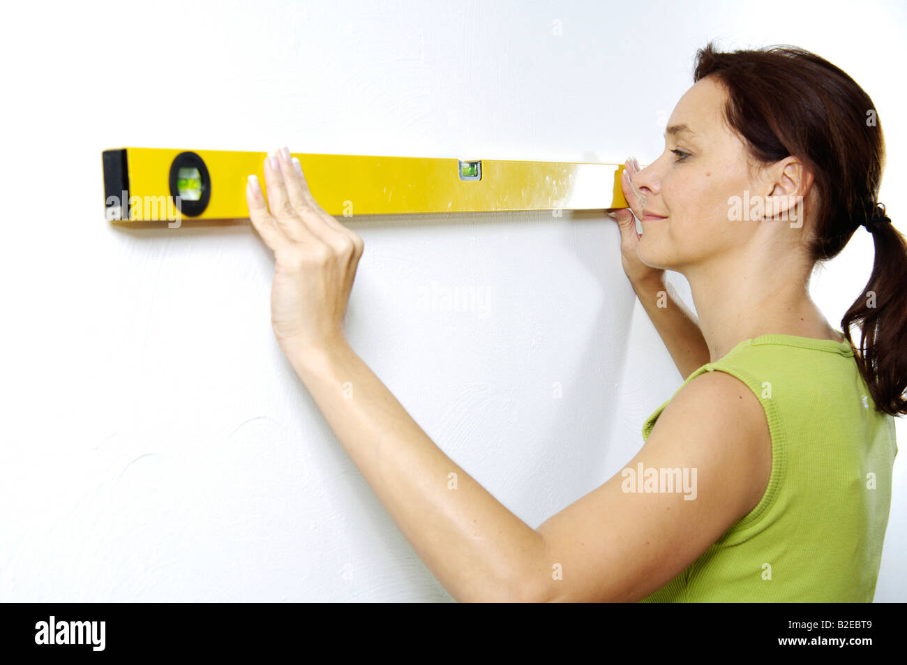 Close-up of woman using spirit level on wall - Stock Image