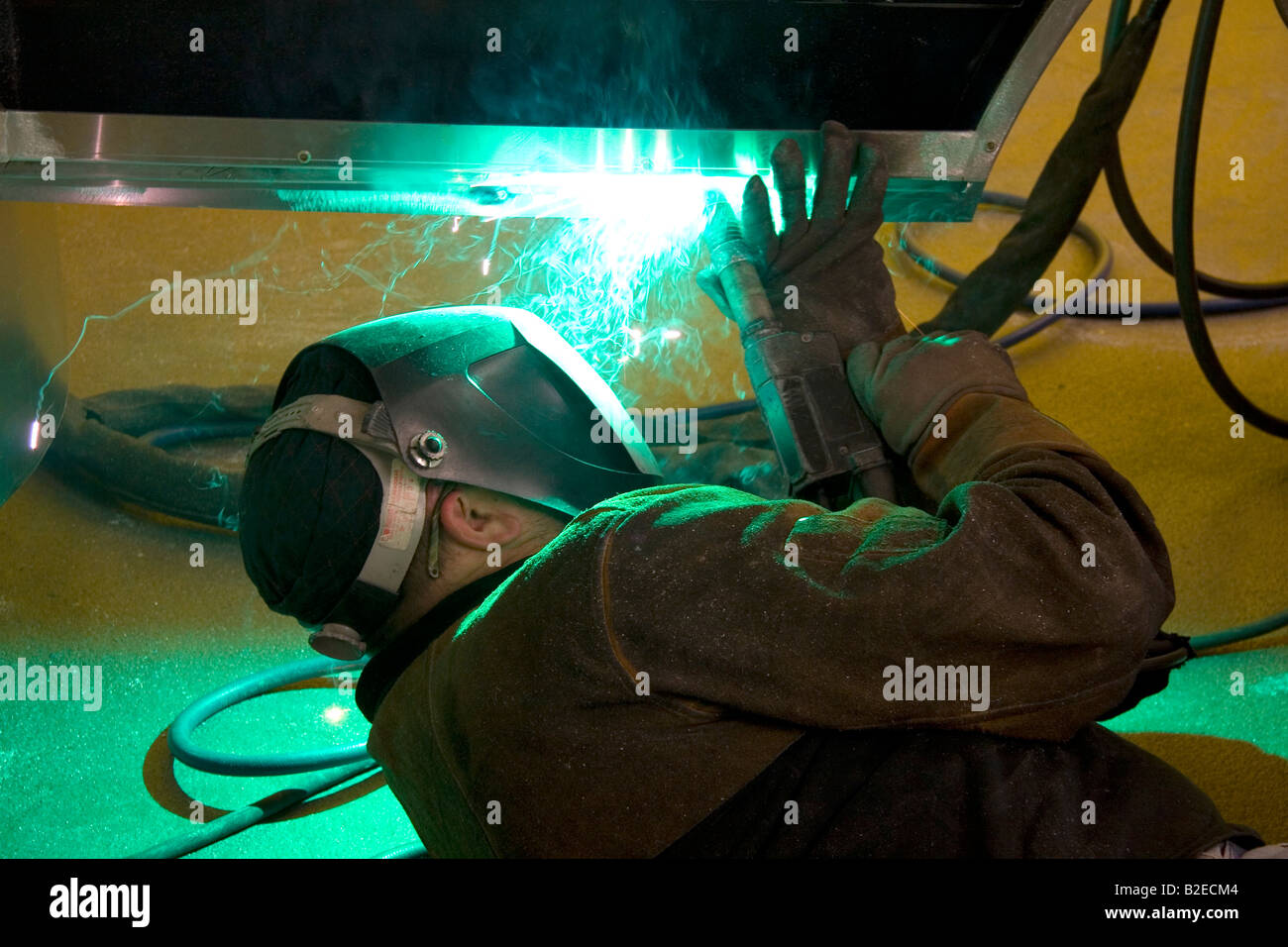 Worker Heliarc welding an aluminum truck chassis at Spartan