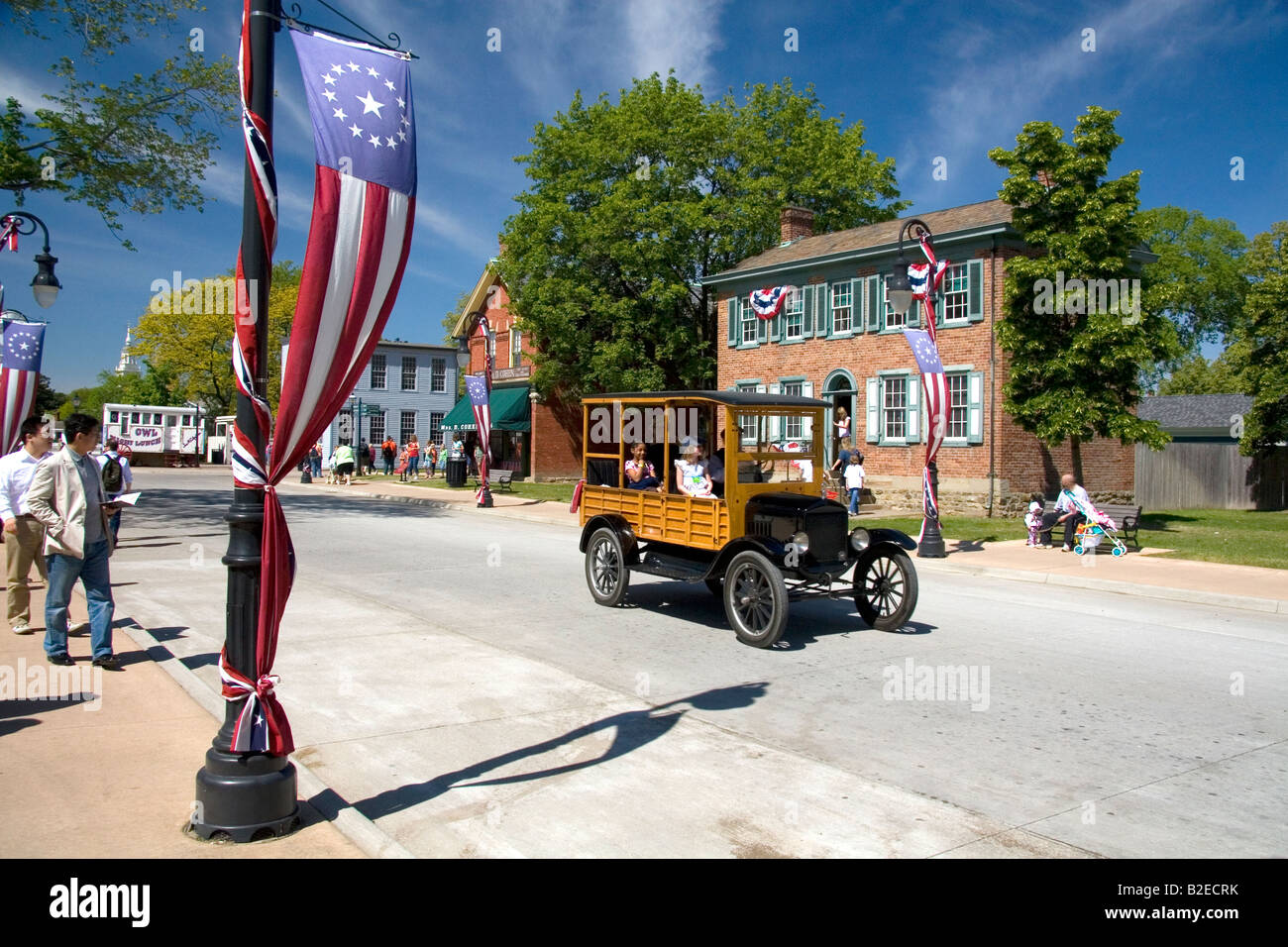 Visitors ride in a Ford Woody on the streets of Greenfield Village at The Henry Ford in Dearborn Michigan - Stock Image
