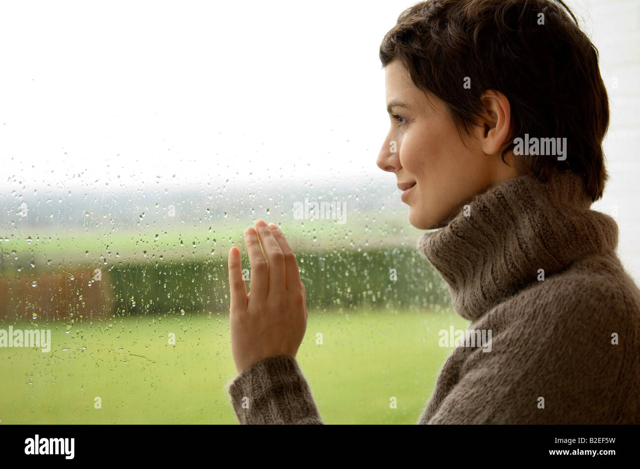 Mid adult woman looking out through a window - Stock Image