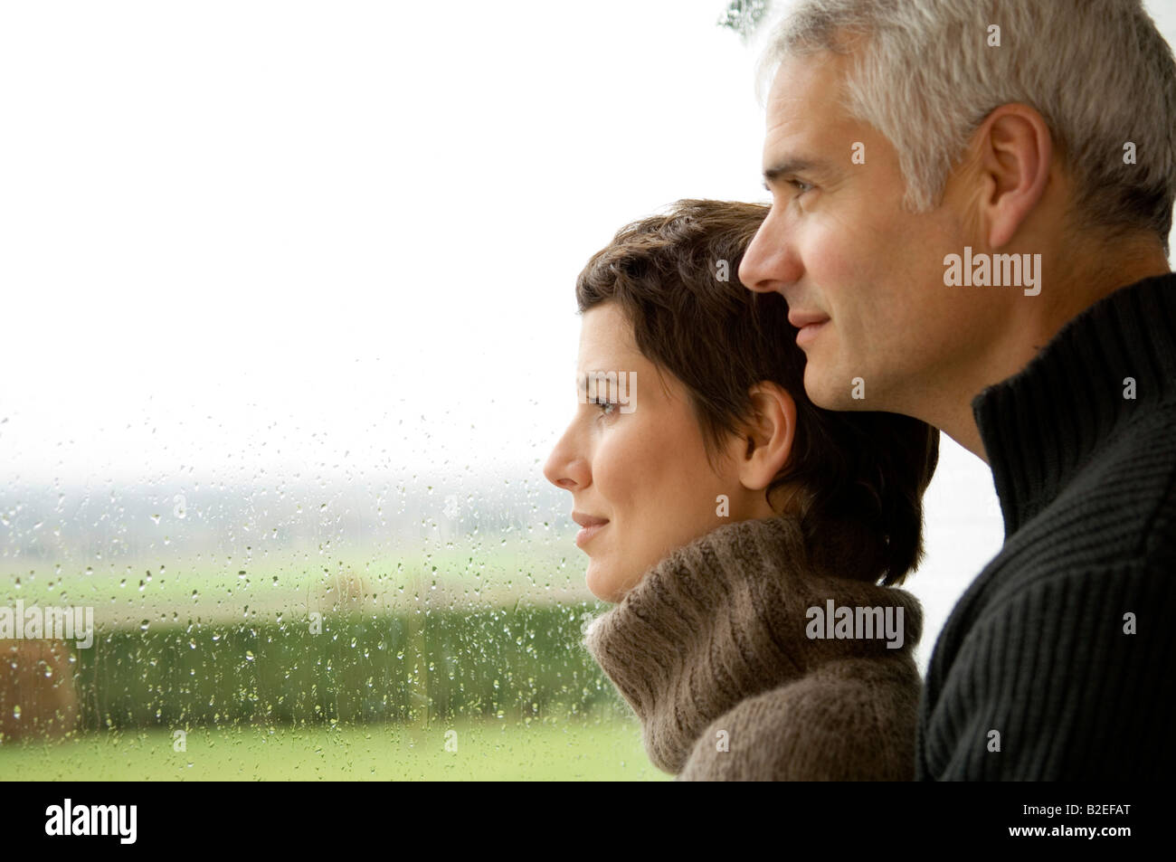 Mature man and a mid adult woman looking out through a window - Stock Image