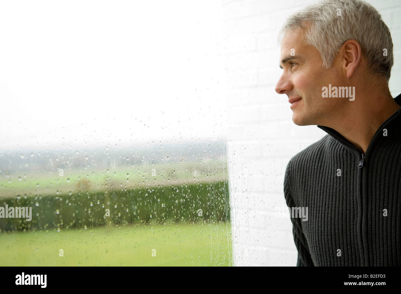 Close-up of a mature man looking out through a window - Stock Image