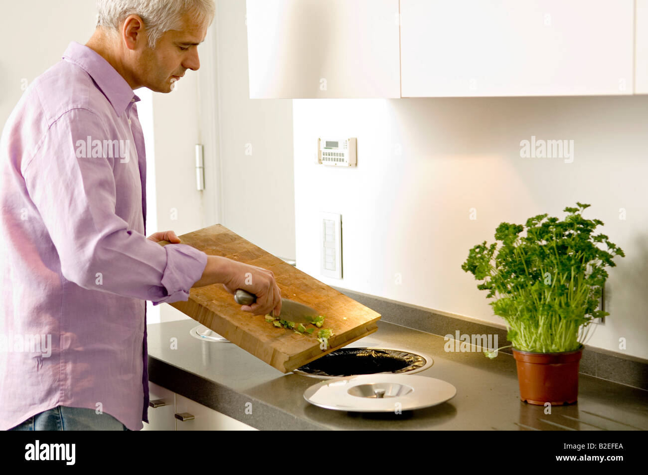 Mature man scraping vegetables pieces into a garbage bin - Stock Image