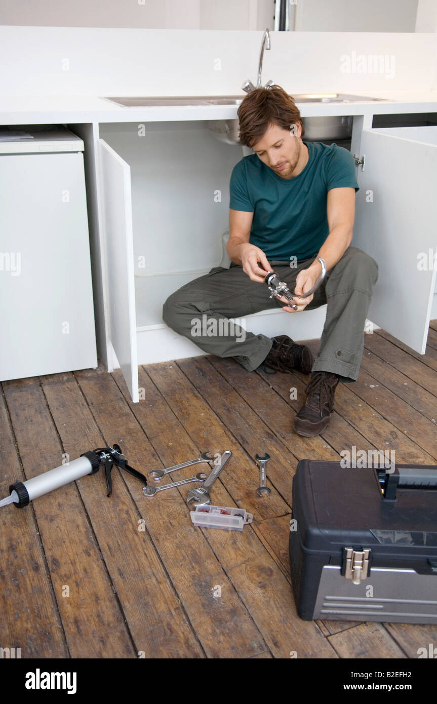 Mid adult man repairing a faucet in the kitchen - Stock Image
