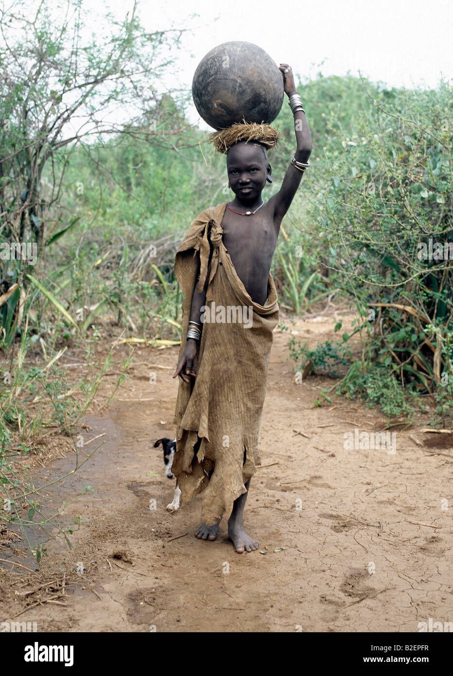 A Mursi girl, accompanied by her dog, carries a large clay pot to collect water from the Omo River. Stock Photo