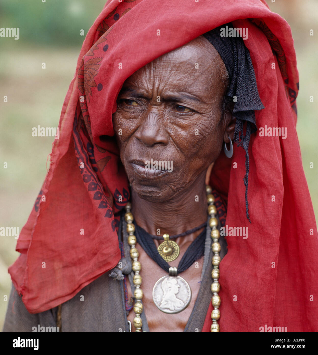 An old Oromo woman wears a brass necklace and pendant, and a silver pendant made from a Maria Theresa thaler. - Stock Image
