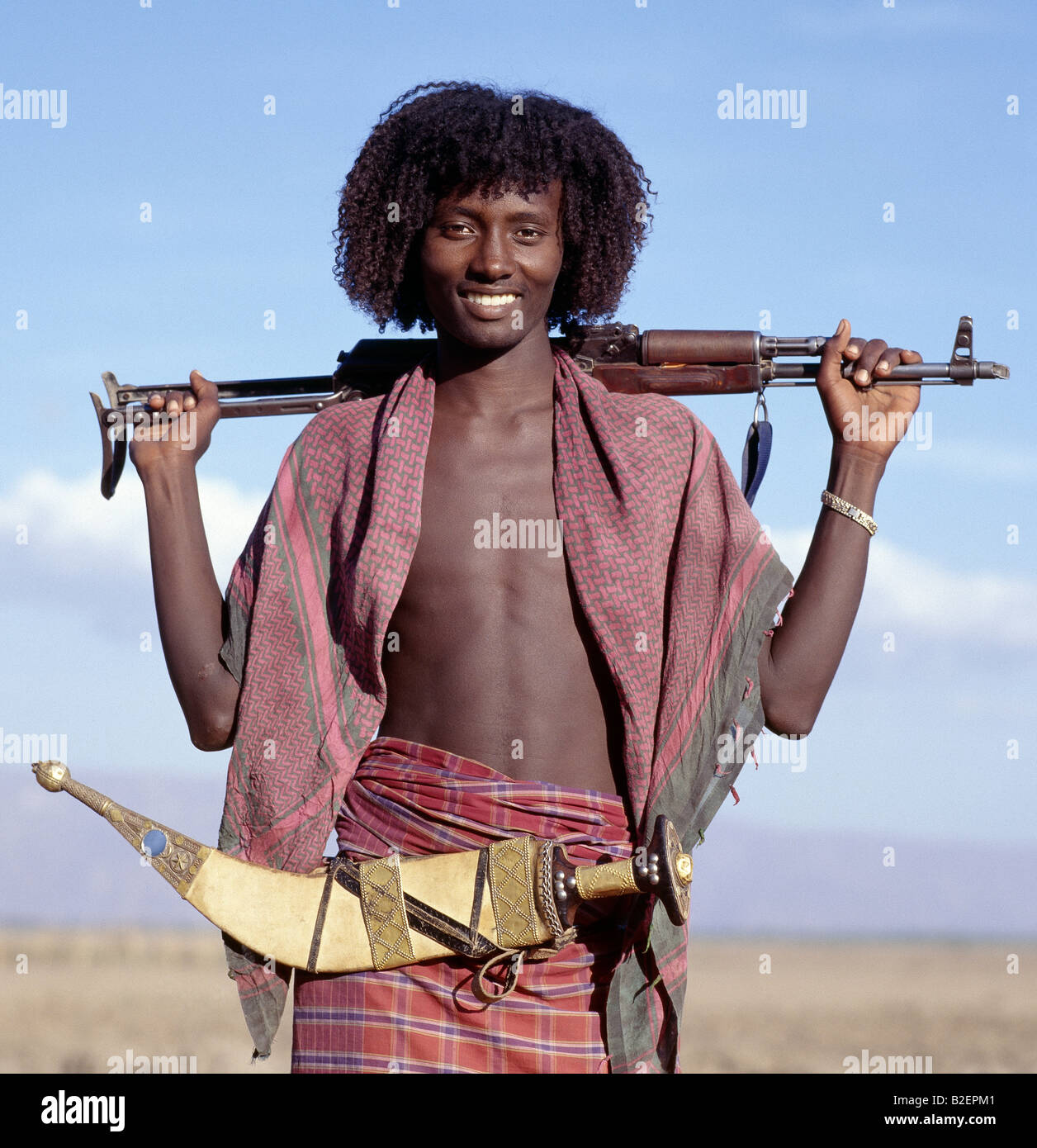 Warriors of the nomadic Afar tribe wear their hair long and carry large curved daggers, known as jile, strapped - Stock Image