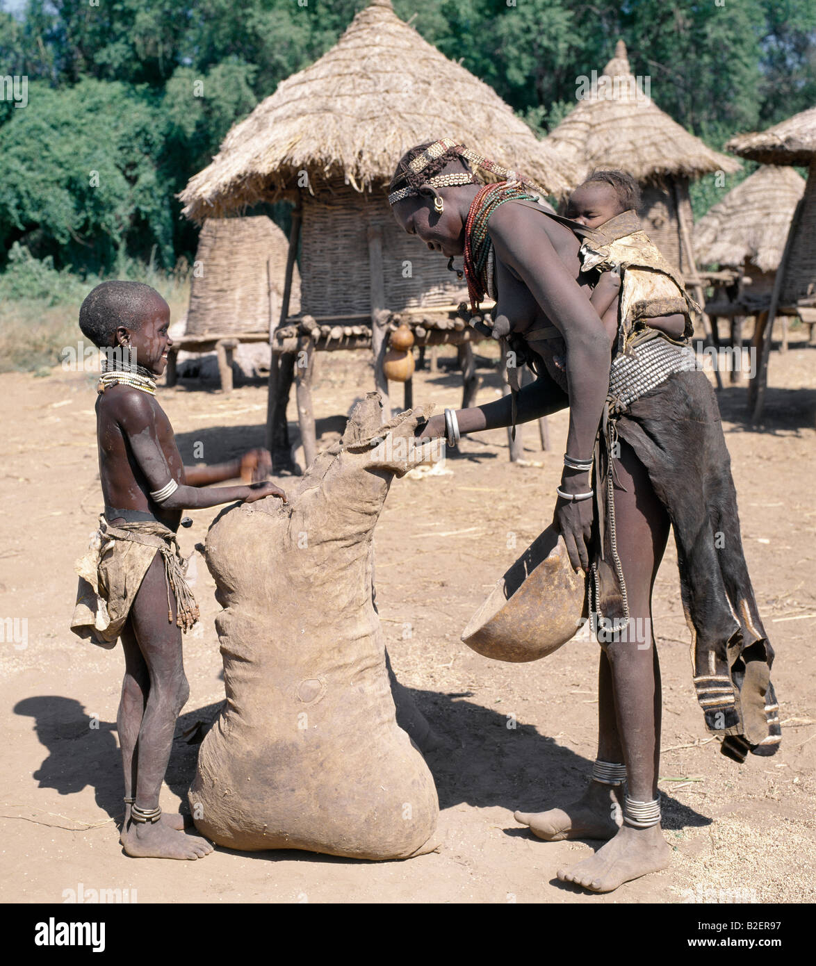 A daughter helps her mother to remove sorghum from a large leather sack. The mother's young baby sleeps  in - Stock Image