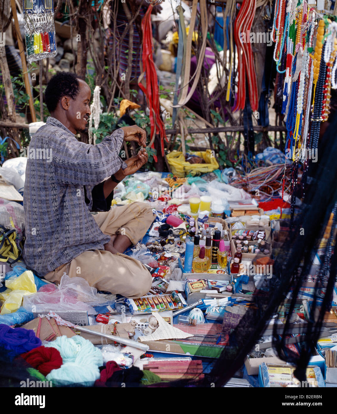 A stallholder surrounded by his wares at Bati market - situated on top of the western scarp of the Abyssinian Rift. - Stock Image