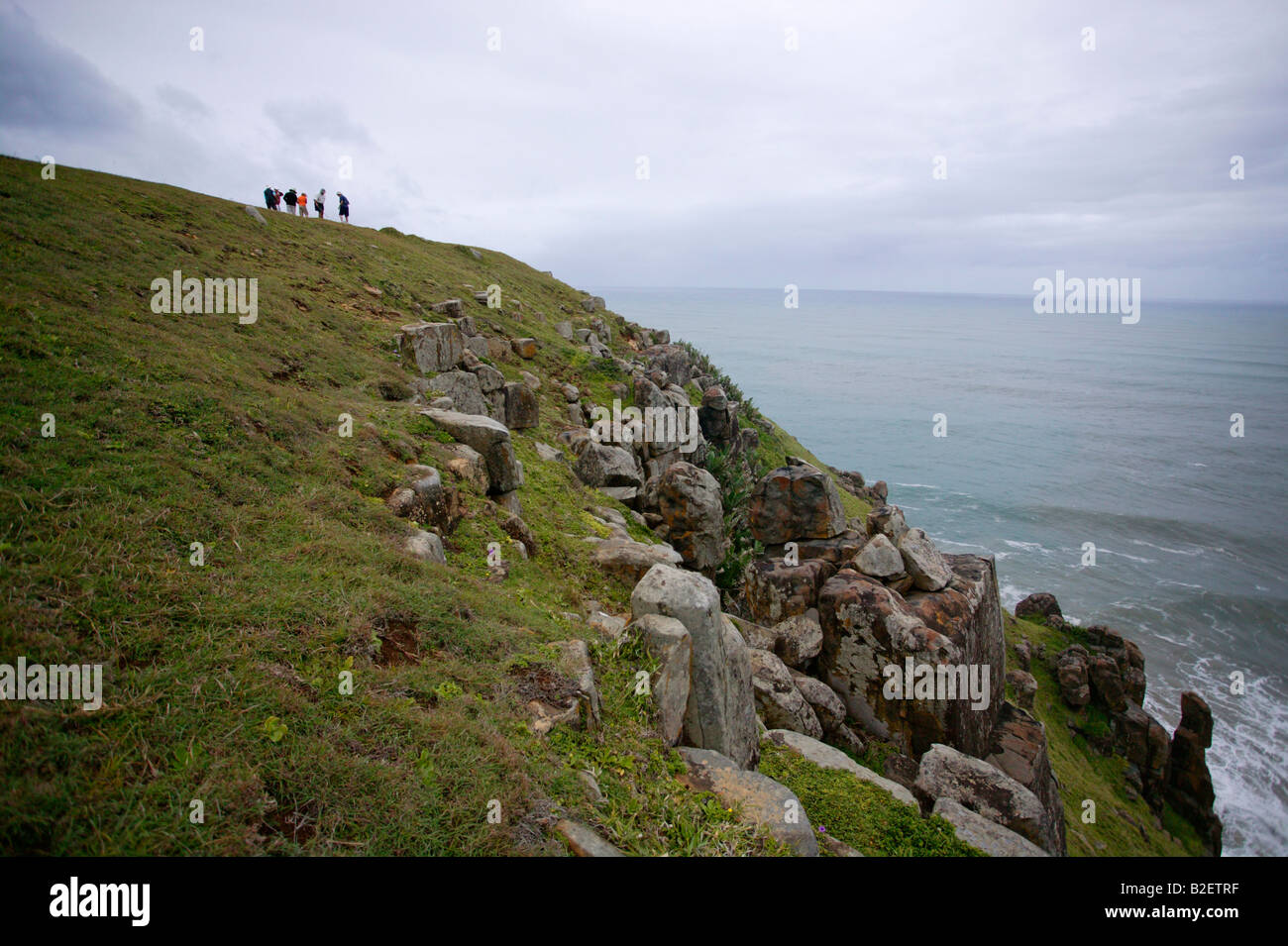 A group of sightseers on a grassy slope overlooking the Morgan bay cliffs and sea - Stock Image