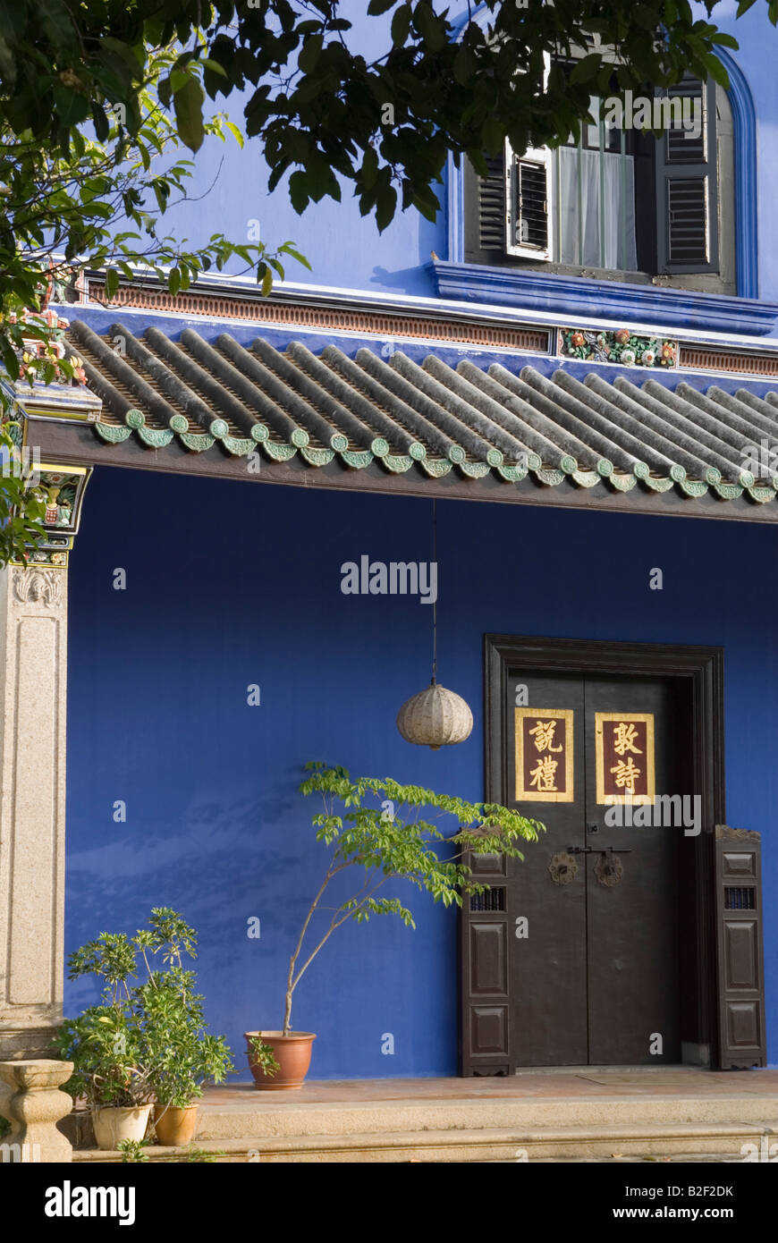 The indigo blue walls and plant decorated courtyard of restored Cheong Fatt Tze Mansion, now a hotel and museum, - Stock Image