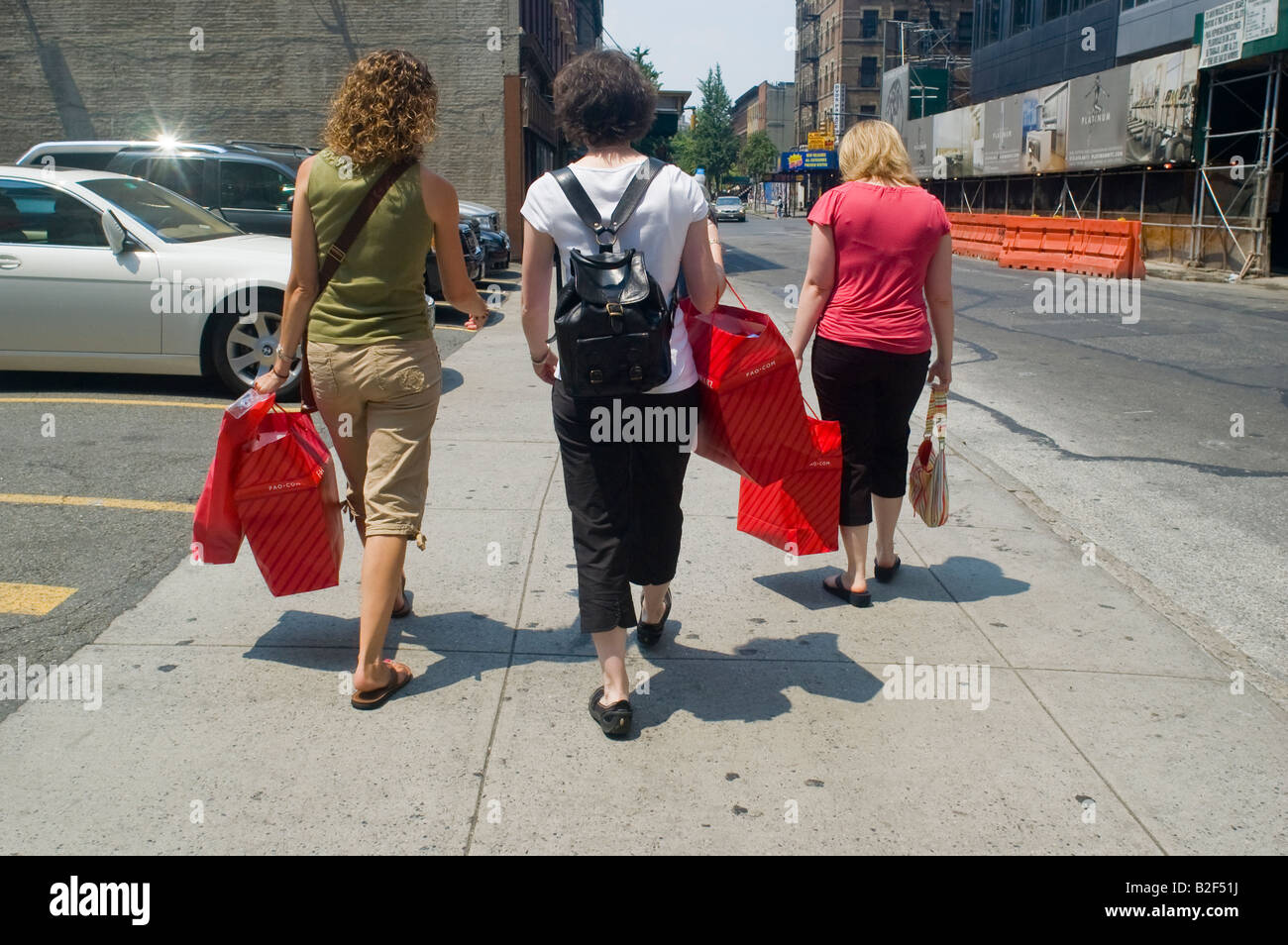 Shoppers walk down a street in Midtown in New York with their purchases from FAO Schwarz - Stock Image