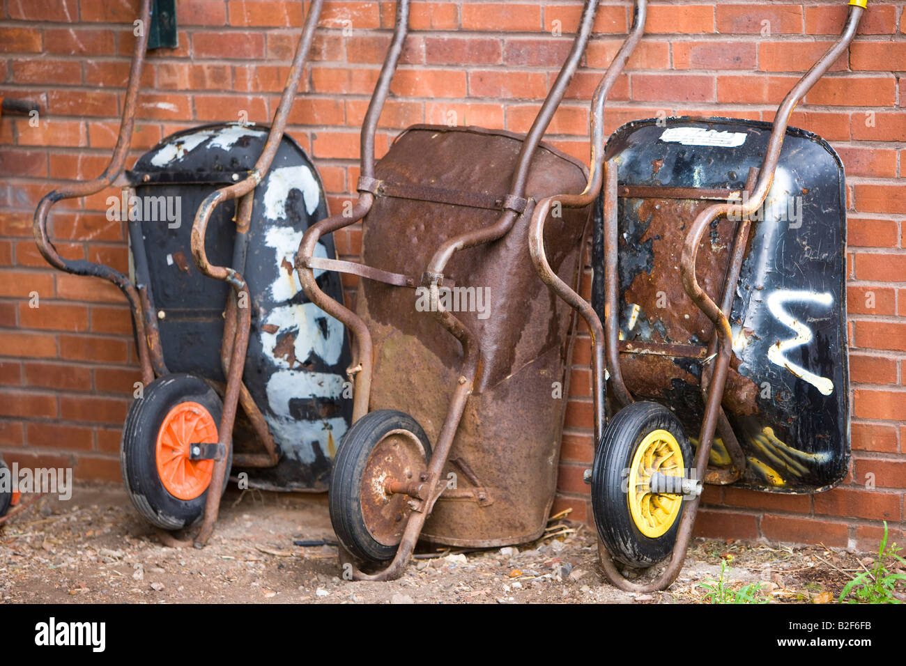 3 wheelbarrows against a wall in an allotment - Stock Image