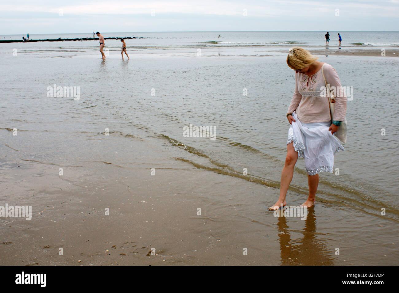 Young woman blonde teen girl walking bare feet in shallow water of sea  beach Scheveningen, Den Haag Hague Netherlands