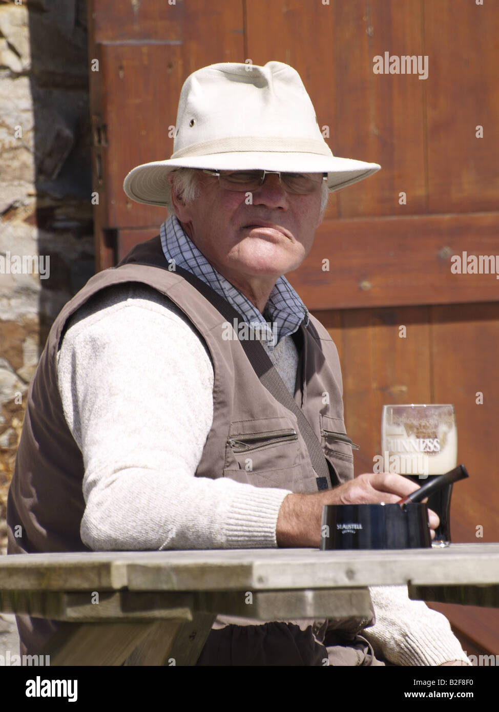 Grey haired old man, wearing a hat and holding a pint in his hand, looking toward the camera with a sour expression. - Stock Image