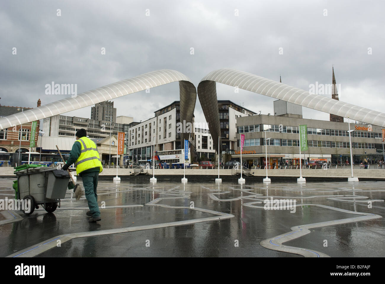 A street sweeper pushes his cart past the Whittle Arches near the Coventry Transport Museum, Millennium Place, Coventry. - Stock Image