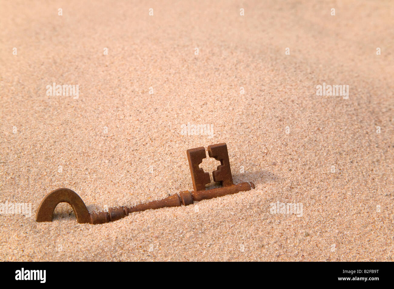 A rusty old key part buried in sand - Stock Image